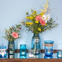 Assortment of colored mason jars filled with flowers and candles
