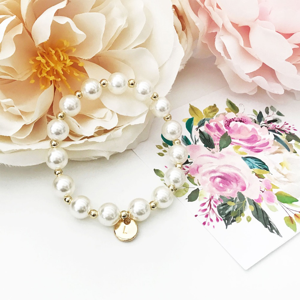 This engraveable silver charm adds to this elegant three strand pearl bracelet.