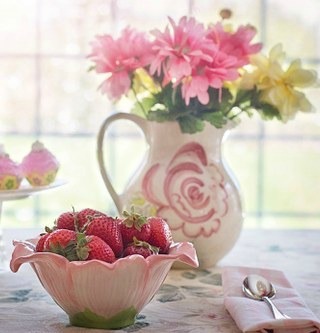 bowl of strawberries with pitcher of flowers behind