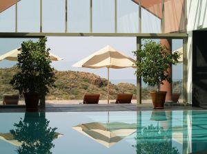 Serene setting with pool, umbrella, beach chairs
